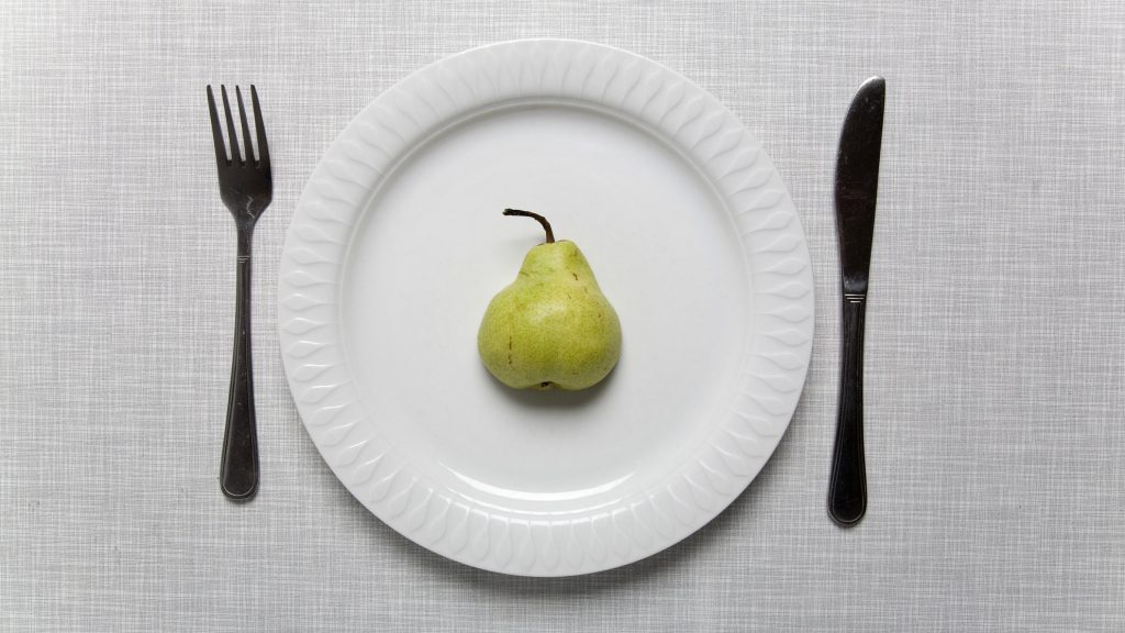 Pear on a plate with fork and knife